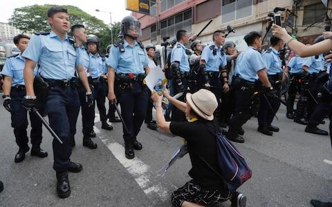 A supporter begs police officer not to attack protesters - Credit: AP
