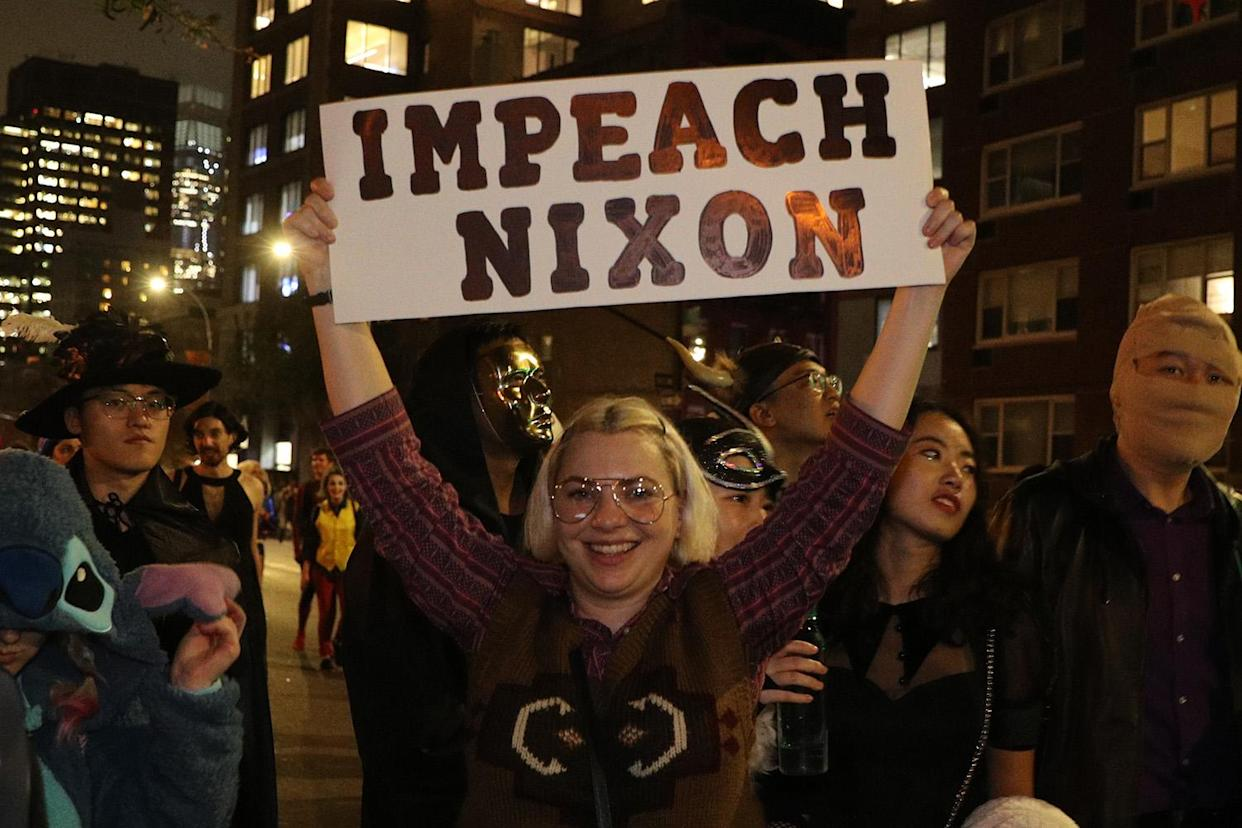 "A reveler holds up an ""Impeach Nixon"" sign while marching in the Village Halloween Parade in New York City. (Photo: Gordon Donovan/Yahoo News)"
