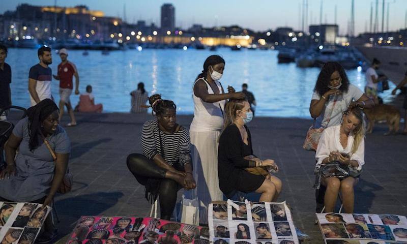 People have their hair braided at the old port in Marseille.