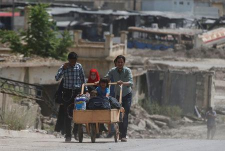 A displaced Iraqi pushes a wheelbarrow with children on their way home after the end of the battles between the Iraqi forces and Islamic State militants at their district in western Mosul, Iraq, April 30, 2017. REUTERS/Muhammad Hamed