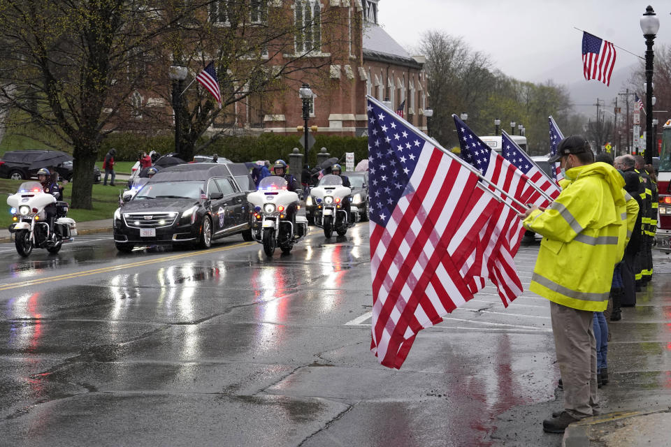 """A hearse carrying the coffin of the late U.S. Capitol Police officer William """"Billy"""" Evans, left, drives past people holding flags while escorted by motorcycles though Adams, Mass., following a funeral Mass for Evans, Thursday, April 15, 2021. Evans, a member of the U.S. Capitol Police, was killed on Friday, April 2, when a driver slammed his car into a checkpoint he was guarding at the Capitol. (AP Photo/Steven Senne)"""