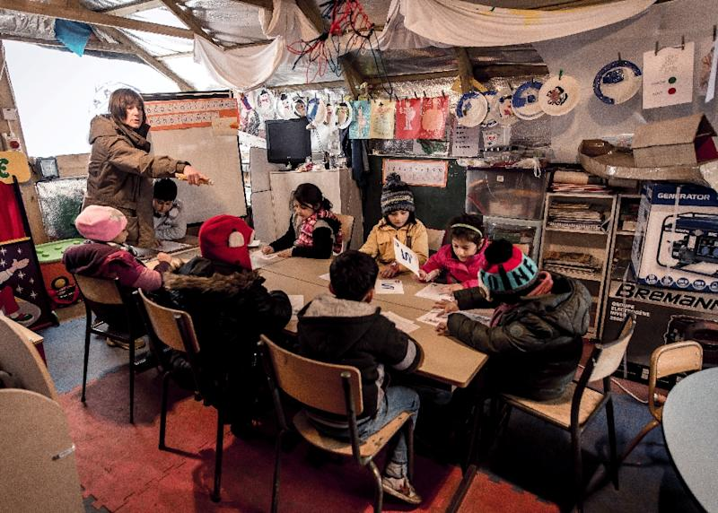 """Migrant children attend a lesson in a makeshift school in the so-called """"Jungle"""" migrant camp in Calais in February 2016 (AFP Photo/Philippe Huguen)"""