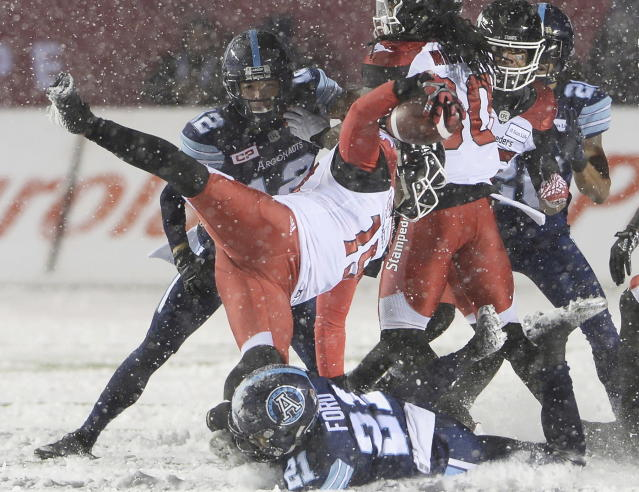 Calgary Stampeders quarterback Bo Levi Mitchell (19) is hit by Toronto Argonauts defensive back Qudarius Ford (21) during the first half of a CFL football game in the Grey Cup in Ottawa on Sunday, Nov. 26, 2017. (Ryan Remiorz/The Canadian Press via AP)