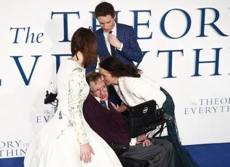 """FILE PHOTO: Jane Wilde Hawking kisses her ex-husband Stephen Hawking as she arrives at the UK premiere of the film """"The Theory of Everything"""" which is based around Stephen Hawking's life, at a cinema in central London December 9, 2014. Actors Eddie Redmayne and Felicity Jones, who play Stephen and Jane in the film, look on. REUTERS/Andrew Winning"""