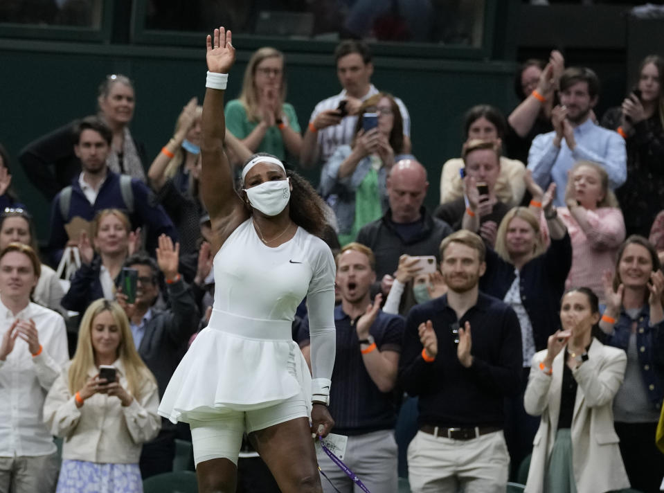 Serena Williams of the US waves as she leaves the court after retiring from the women's singles first round match against Aliaksandra Sasnovich of Belarus on day two of the Wimbledon Tennis Championships in London, Tuesday June 29, 2021. (AP Photo/Kirsty Wigglesworth)