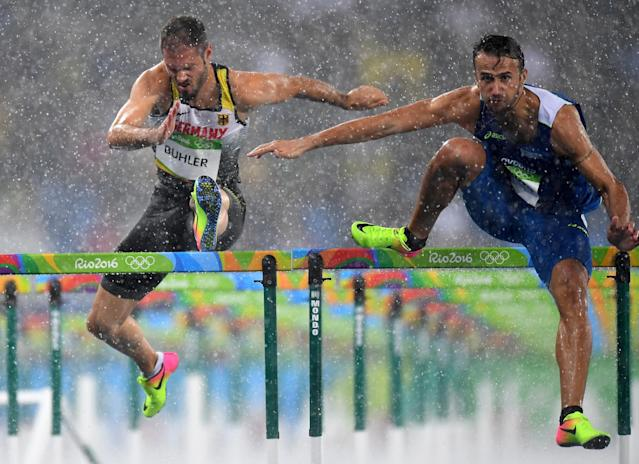 <p>Matthias Buhler of Germany and Milan Trajkovic of Cyprus compete in the rain during the Men's 110m Hurdles Round 1 – Heat 2 on Day 10 of the Rio 2016 Olympic Games at the Olympic Stadium on August 15, 2016 in Rio de Janeiro, Brazil. (Getty) </p>