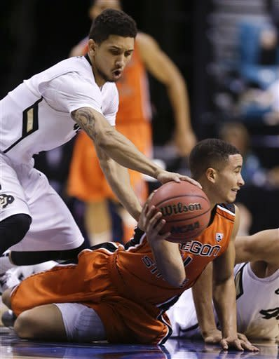 Colorado's Askia Booker, left, tries to strip the ball as Oregon State's Challe Barton looks to pass in the second half during a Pac-12 tournament NCAA college basketball game on Wednesday, March 13, 2013, in Las Vegas. Colorado won 74-68. (AP Photo/Julie Jacobson)