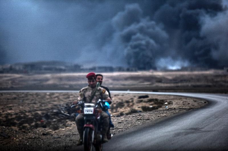 An Iraqi soldier and a civilian ride a motorbike as smoke rises behind them, on the road between Qayyarah and Mosul on October 28, 2016