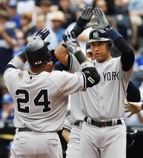 New York Yankees' Robinson Cano (24) is congratulated by Derek Jeter after his grand slam during the third inning of a baseball game against the Kansas City Royals in Kansas City, Mo., Sunday, May 6, 2012. (AP Photo/Orlin Wagner)