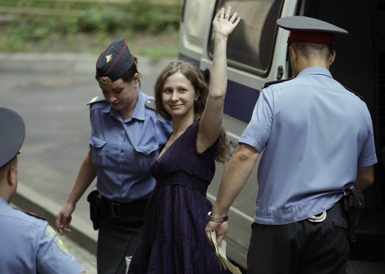 "Yekaterina Samutsevich, center, a member of feminist punk group Pussy Riot waves as she is escorted to a court room in Moscow, Russia, Monday, July 30, 2012. Three members of the band are facing trial for performing a ""punk prayer"" against Vladimir Putin from a pulpit of Moscow's main cathedral before Russia's presidential election in March, in which he won a third term. (AP Photo/Mikhail Metzel)"