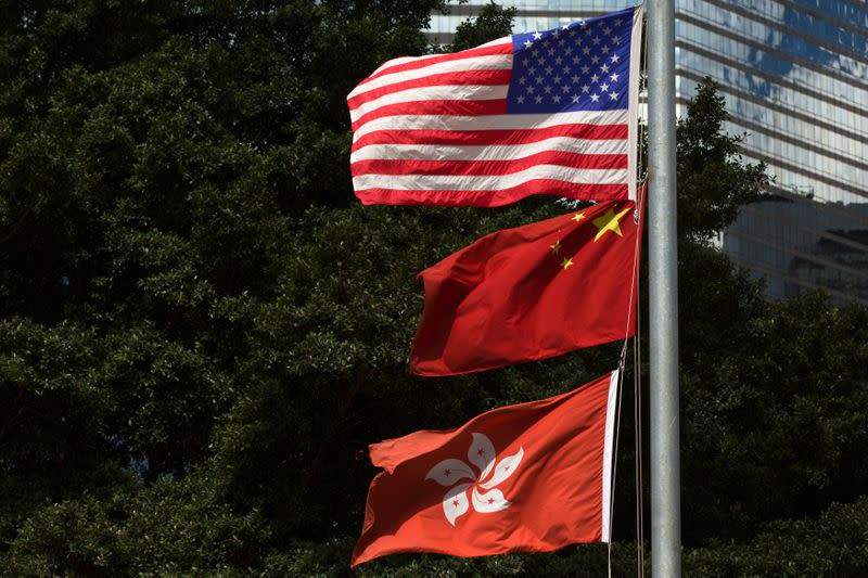 FILE PHOTO: Flags of China, Hong Kong and the U.S. fly next to each other along Fenwick Pier, in Hong Kong