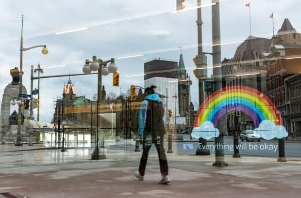 Parliament Hill's Peace Tower and the National War Memorial are reflected in a window at the National Arts Centre in Ottawa, in front of a digital screen displaying an image of a rainbow with the message,