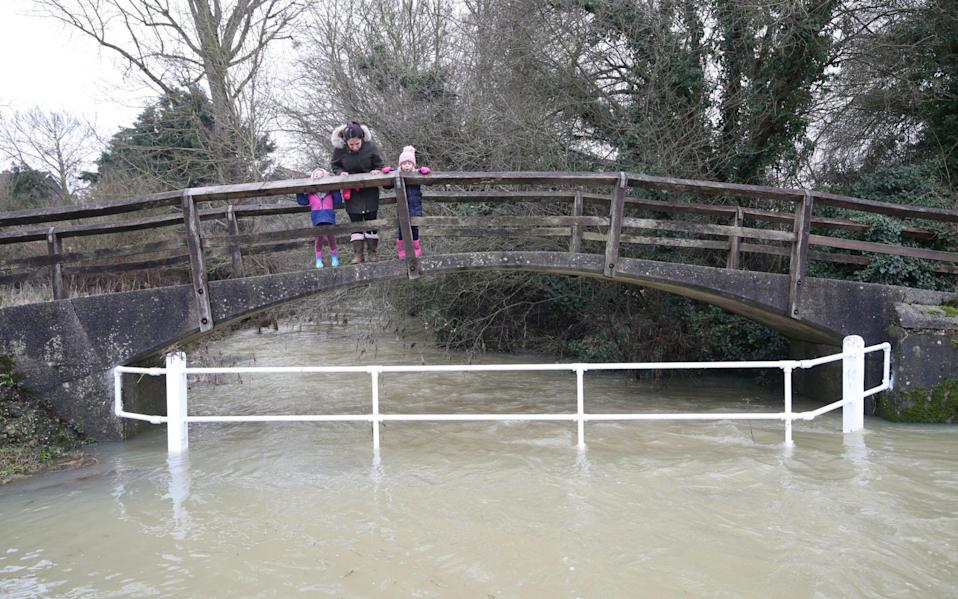 People crossing a bridge over a flooded river in Great Easton, Essex - Yui Mok/PA