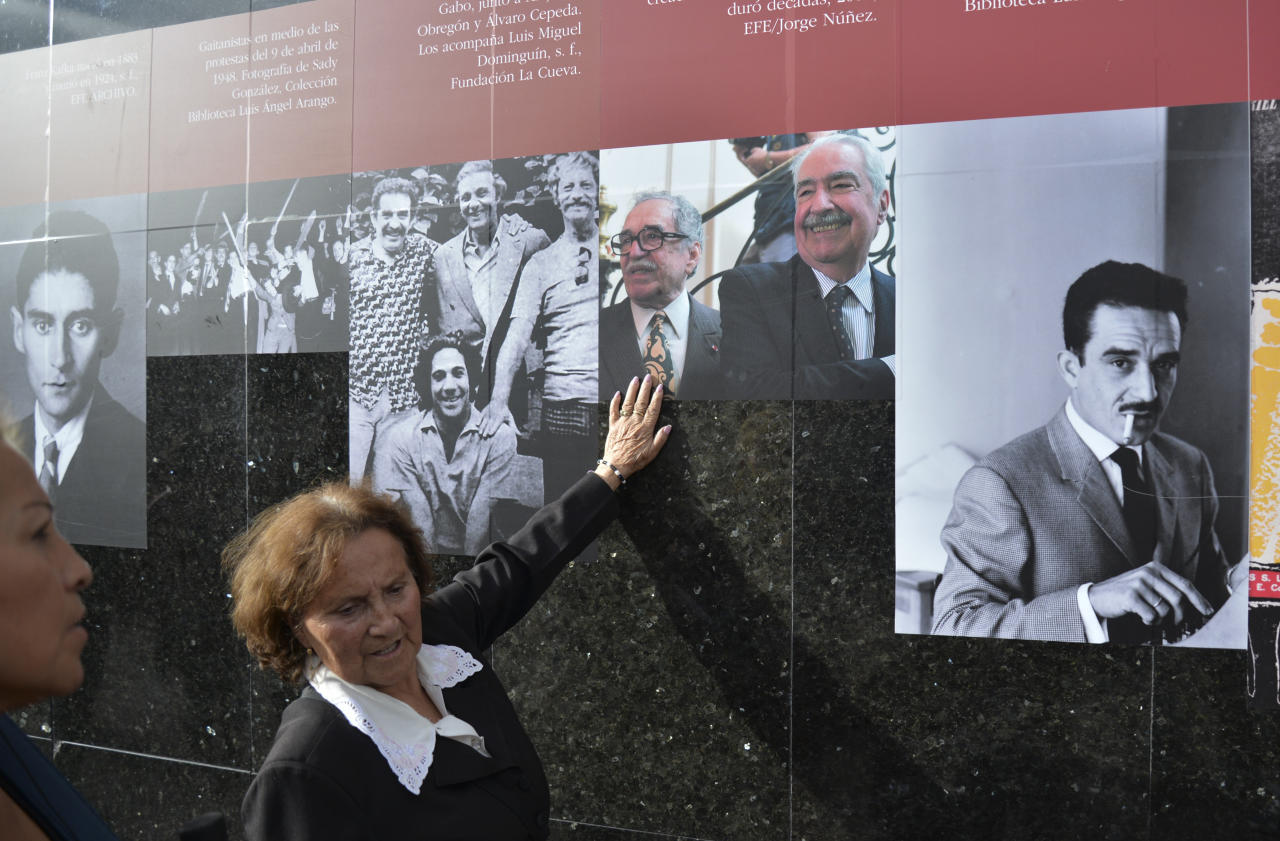 A woman touches photos on a timeline of the life of Colombian Nobel laureate Gabriel Garcia Marquez on a wall at the Luis Angel Arango Library in downtown Bogota, Colombia, Thursday, April 17, 2014. Garcia Marquez died in Mexico City on Thursday. The author was among Latin America's most popular writers and widely considered the father of a literary style known as magic realism. (AP Photo/Diana Sanchez)