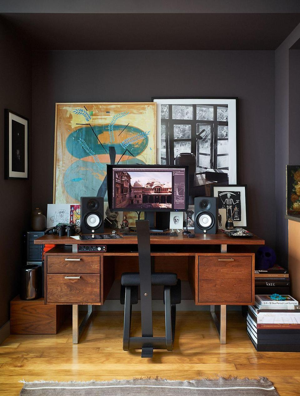 <p>An architectural alcove is the perfect place to dedicate to your home office. In photographer Bjorn Wallander's New York City apartment, he painted this nook in a soothing deep espresso color but then brightened things up with plenty of artwork and books for inspiration. And don't forget to add speakers (with your housemates's permission, of course). </p>