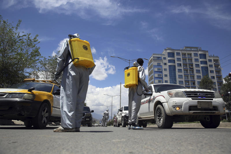 Image: Volunteers in protective suits spray disinfectant on passing vehicles to help curb the spread of the coronavirus in Kabul, Afghanistan (Rahmat Gul / AP)