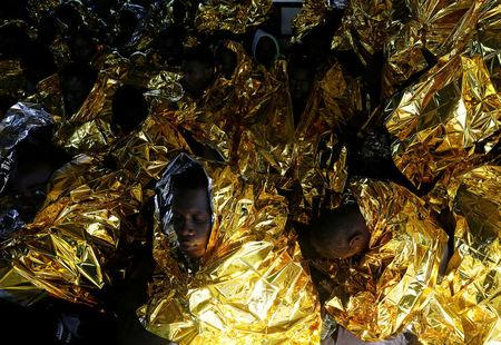 Migrants rest on the deck of the Malta-based NGO Migrant Offshore Aid Station (MOAS) ship Phoenix after being rescued from a rubber dinghy in the central Mediterranean in international waters some 15 nautical miles off the coast of Zawiya in Libya, April 14, 2017.    REUTERS/Darrin Zammit Lupi        TPX IMAGES OF THE DAY