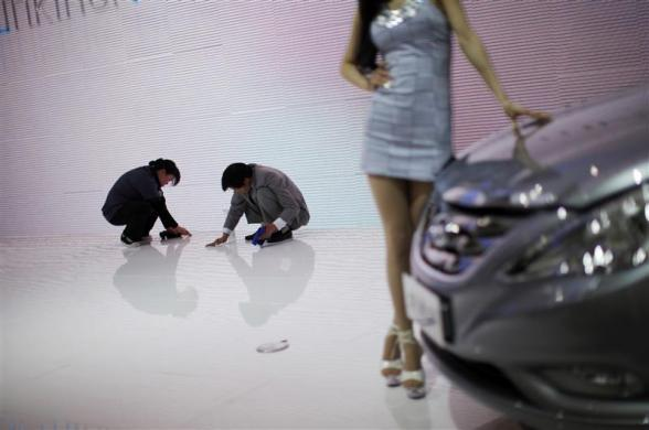Employees clean the floor as a model poses next to a vehicle during the 14th Shanghai International Automobile Industry Exhibition April 20, 2011.