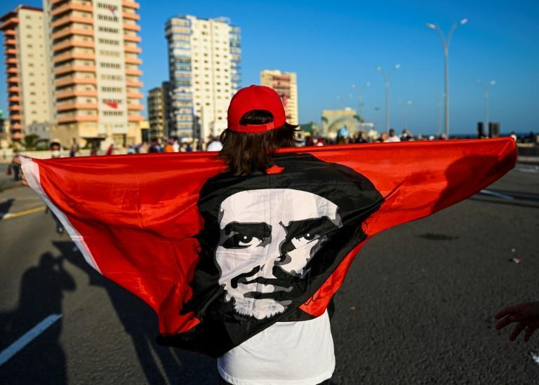 A woman holds a flag with the image of late Argentinian revolutionary Che Guevara in Havana, on July 17, 2021