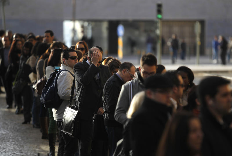 In this picture taken Nov.19 2013, commuters in Lisbon wait to board buses during a subway workers' strike. Unlike the rioting in Athens, protests in Portugal have been peaceful like those in Dublin. (AP Photo/Francisco Seco)