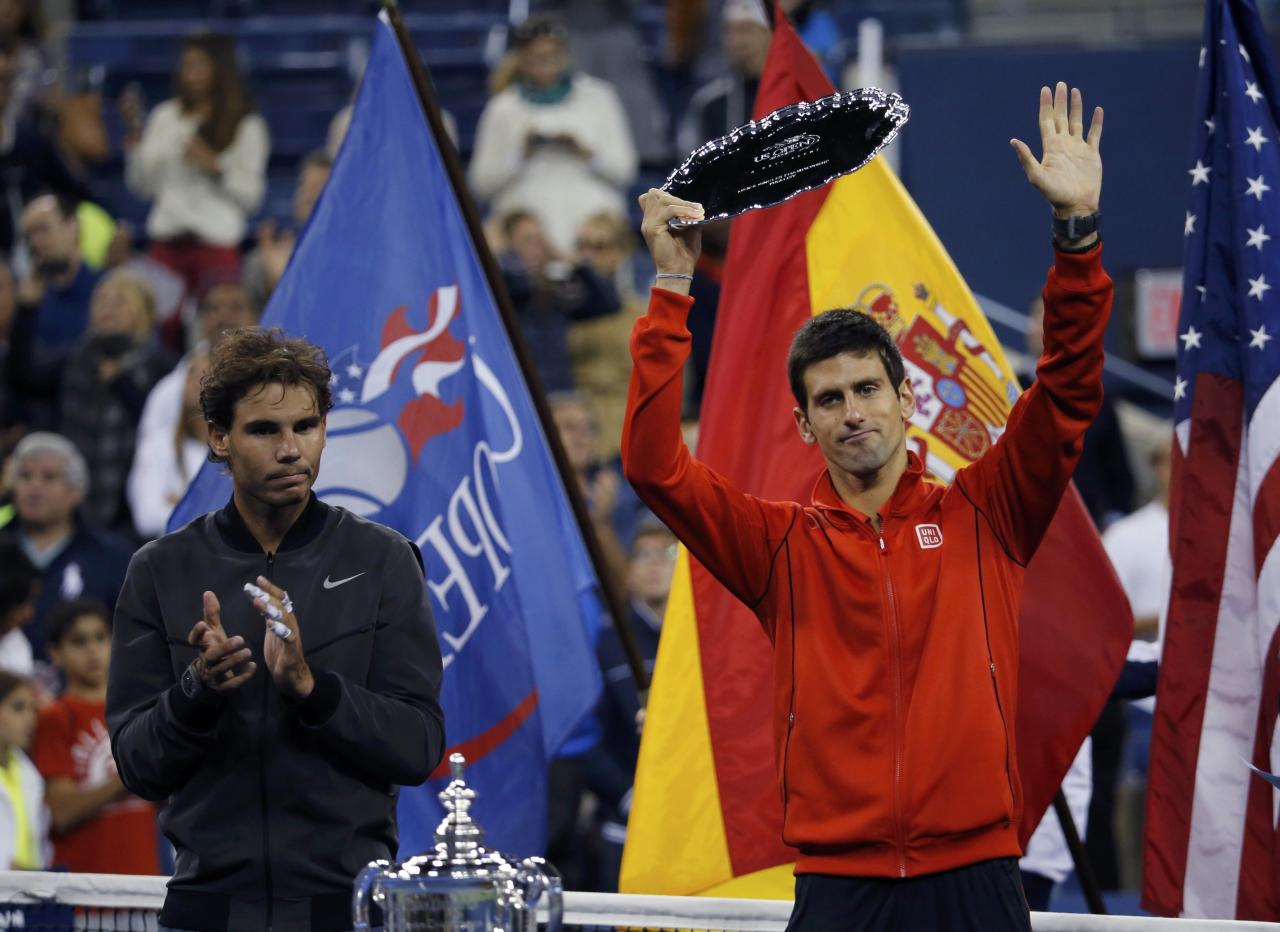 Rafael Nadal of Spain applauds as Novak Djokovic of Serbia raises his runner up trophy after Nadal won their men's final match at the U.S. Open tennis championships in New York, September 9, 2013. REUTERS/Ray Stubblebine (UNITED STATES - Tags: SPORT TENNIS)