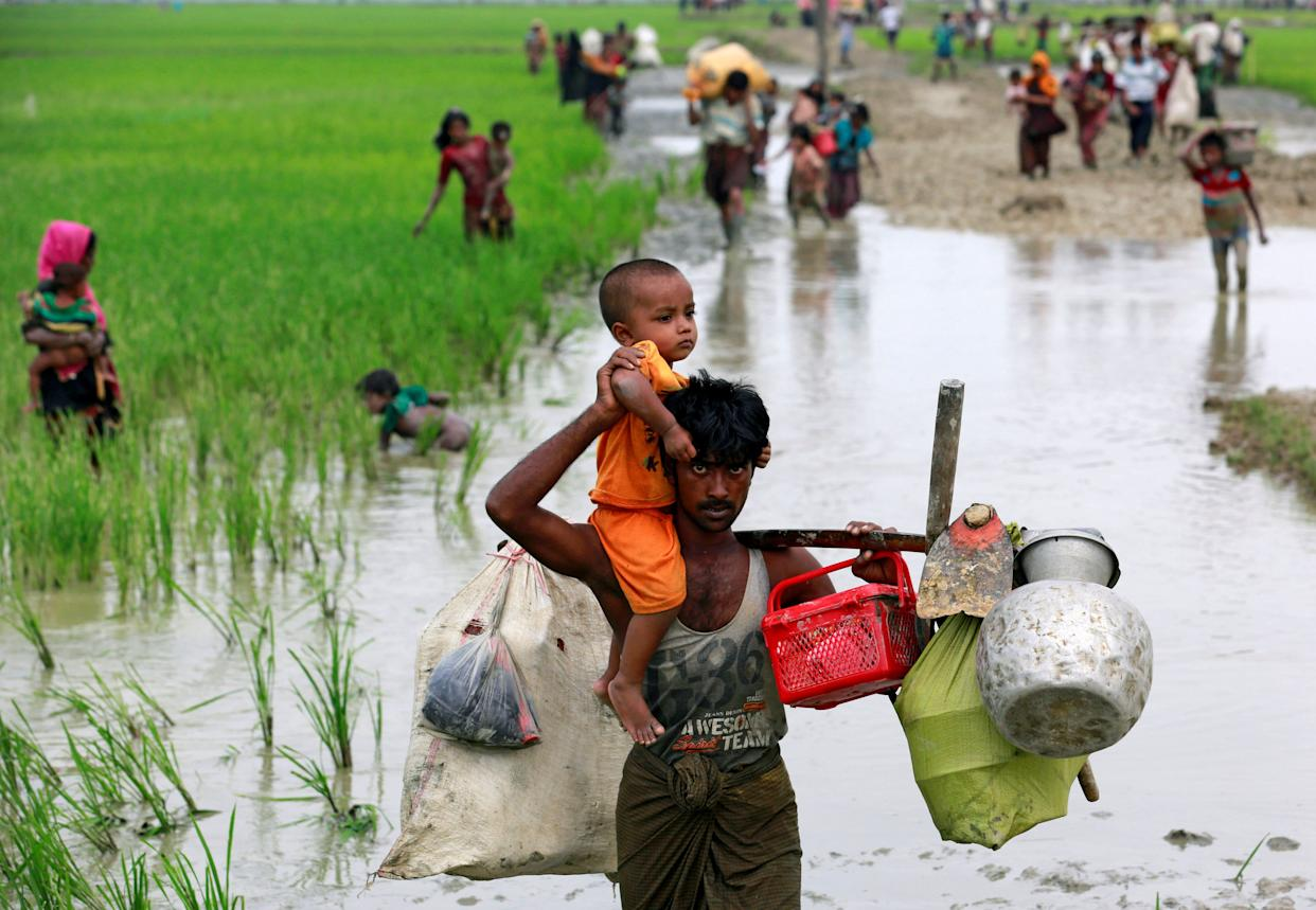 A Rohingya refugee carries a child through a paddy field after crossing the Bangladesh-Myanmar border, in Teknaf, Bangladesh, on Sept. 6, 2017.