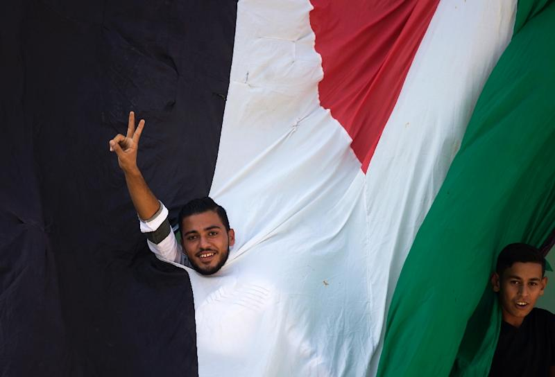 A Gazan flashes a victory sign behind a large Palestinian flag as he and others await the arrival of prime minister Rami Hamdallah on a visit that has raised hopes of an end to a decade-long split