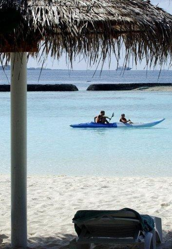 File photo shows tourists in a kayak off Kurumba island, Maldives. Dozens of tiny islands in the Maldives are battling rising sea levels that threaten to wipe them off the face of the earth