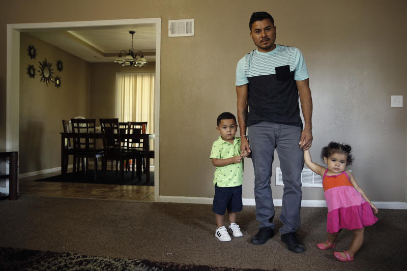 In this photo taken Tuesday, Aug. 28, 2018, Louis Alberto Enamorado Gomez stands with his daughter, Jeydi, 1, and son, Justin, 3, at their home in Grandview, Mo. Living in the U.S. since 2005, Gomez is fighting a deportation order stemming from a 2012 DUI charge because he fears what his removal would mean for his seven children, all U.S. citizens for whom he is the sole provider. (AP Photo/Charlie Riedel)