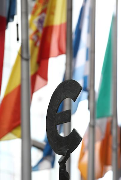 A statue holding the Euro sign is pictured with some flags of EU countries outside the European Parliament building in Brussels, Friday, Oct. 12, 2012. The European Union won the Nobel Peace Prize on Friday for its efforts to promote peace and democracy in Europe, despite being in the midst of its biggest crisis since the bloc was created in the 1950s. (AP Photo/Yves Logghe)