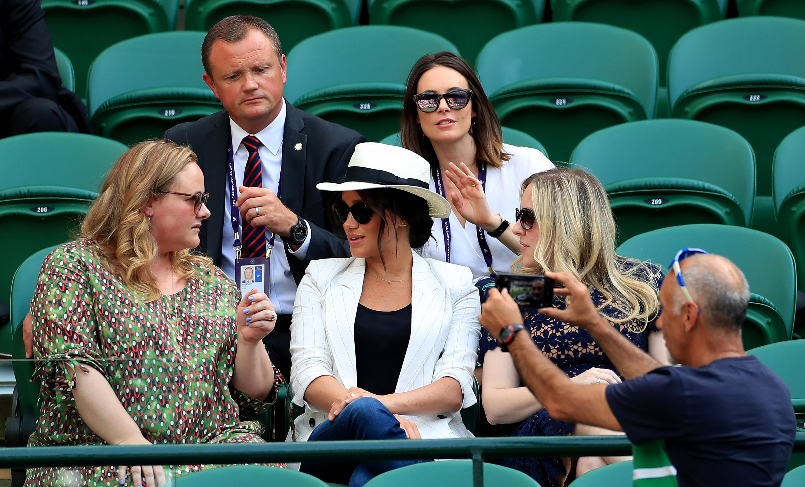 A spectator takes a selfie as the Duchess of Sussex watches the Serena Williams match on court one during day four of the Wimbledon Championships at the All England Lawn Tennis and Croquet Club, Wimbledon. (Photo by Mike Egerton/PA Images via Getty Images)