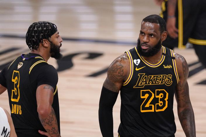Los Angeles Lakers' Anthony Davis (3) and LeBron James (23) talk on the floor during the second half of Game 2 of basketball's NBA Finals, Friday, Oct. 2, 2020, in Lake Buena Vista, Fla. (AP Photo/Mark J. Terrill)