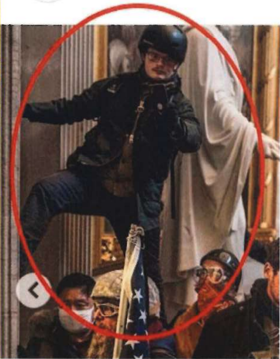 In this New York Times Magazine image taken from an FBI document, a man believed to be Stephen Ethan Horn of Wake Forest stands over other people with a cellphone in his left hand inside the U.S. Capitol on Jan. 6, 2021.