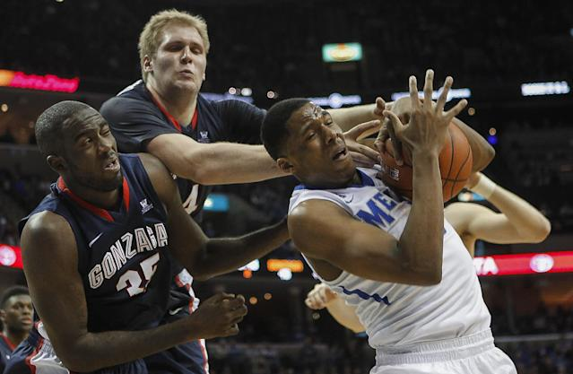 Memphis forward Nick King, right, tries to hang onto a rebound against Gonzaga center Sam Dower Jr. (35) and center Przemek Karnowski, back, in the second half of an NCAA college basketball game on Saturday, Feb. 8, 2014, in Memphis, Tenn. Memphis won 60-54. (AP Photo/Lance Murphey)