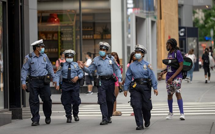 Traffic officers wearing masks are seen walking in a line down the street as the city moves into Phase 3 of re-opening following restrictions imposed to curb the coronavirus pandemic on July 7, 2020 in New York City. - Alexi Rosenfeld/Getty Images North America