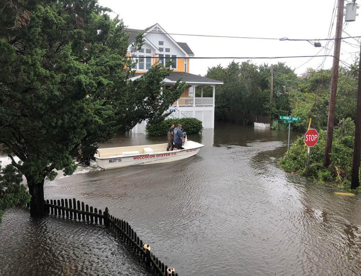 Ocracoke Volunteer Fire Department chief Albert O'Neal, in blue shirt, boats down Sunset Drive on his way to seek out islanders stranded in their flooded homes in the aftermath of Hurricane. Dorian Friday, Sept. 6, 2019 on Ocracoke Island, N.C. (Connie Leinbach/Ocracoke Observer via AP)