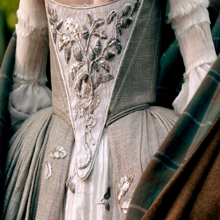 Claire wearing a ballgown dress with a corset and long sleeves