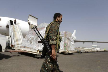 A Houthi militant walks past a shipment of emergency medical aid for the Red Cross being unloaded from a plane at Sanaa airport April 11, 2015. REUTERS/Khaled Abdullah