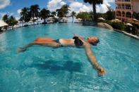Sigal Baram, 54, a newly-arrived tourist from Israel, enjoys in a swimming pool as Phuket reopens to overseas tourists, in Thailand