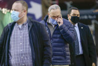 Senate Minority Leader Chuck Schumer, D-N.Y., center, is surrounded by security as he arrives for a news conference, Tuesday, Jan. 12, 2021, in New York. (AP Photo/Mary Altaffer)