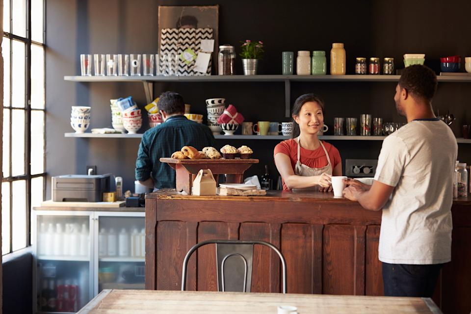 Staff Serving Customer In Busy Coffee Shop (Photo: monkeybusinessimages via Getty Images)