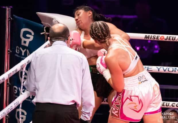 Jeanette Zacarias Zapata, centre, takes a punch from Marie-Pier Houle, right, in a welterweight fight at the IGA stadium in Montreal on Saturday. (Handout/GYM-Yannick Maltais via The Canadian Press - image credit)