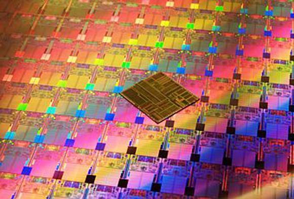 A wafer of Intel processors with a chip on top of the wafer.