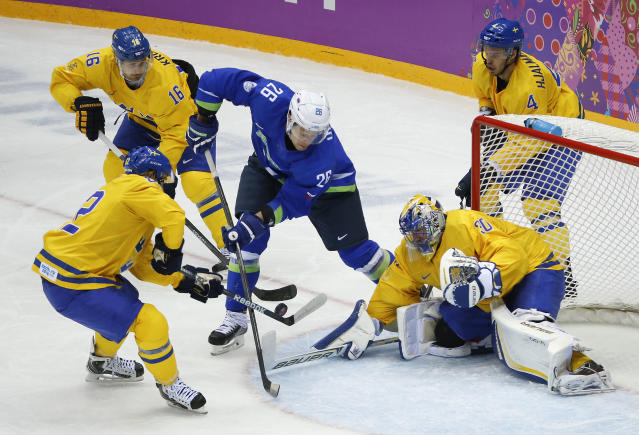 Sweden goaltender Henrik Lundqvist, right, blocks a shot attempt by Slovenia forward Jan Urbas in the second period of a men's ice hockey game at the 2014 Winter Olympics, Wednesday, Feb. 19, 2014, in Sochi, Russia. (AP Photo/Mark Humphrey)