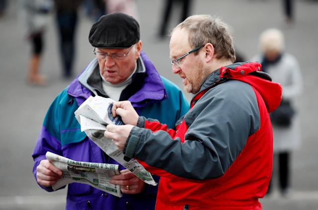 Horse Racing - Grand National Festival - Aintree Racecourse, Liverpool, Britain - April 12, 2018 Racegoers read papers during the Grand National Festival Action Images via Reuters/Jason Cairnduff