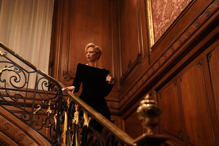 """Carrie Coon stands on an elaborate staircase in """"The Nest."""""""