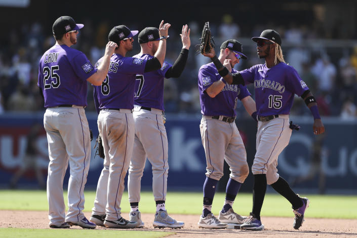 Colorado Rockies, Raimel Tapia, right, celebrates with Garrett Hampson, second from right, Trevor Story, center, Joshua Fuentes, second from left, and C.J. Cron, left, after defeating the San Diego Padres in a baseball game Sunday, July 11, 2021, in San Diego. (AP Photo/Derrick Tuskan)