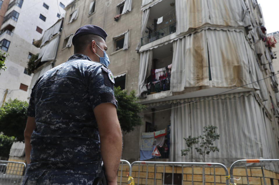 In this Saturday, May 23, 2020 photo, a Lebanese policeman is deployed to enforce isolation outside a building where dozens of foreign workers living in overcrowded apartments have tested positive with the coronavirus, in Beirut, Lebanon. Some 250,000 registered migrant laborers in Lebanon — maids, garbage collectors, farm hands and construction workers — are growing more desperate as a crippling economic and financial crisis sets in, coupled with coronavirus restrictions. With no functioning airports and exorbitant costs of repatriation flights, many are trapped, unable to go home. (AP Photo/Hussein Malla)
