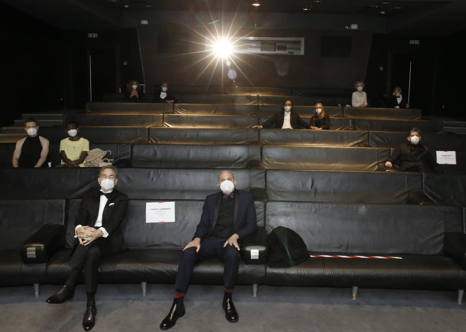 Nominees, including: Yorgos Lamprinos, bottom center, Adrien Merigeau, center left, Amaury Ovise, center right, Nicolas Becker, center, Jean-Louis Livi, top right, and Florian Zeller, top second left, attend a screening of the Oscars on Monday April 26, 2021 in Paris, France. (AP Photo/Lewis Joly, Pool)
