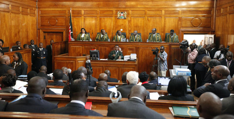 The six Supreme Court judges, led by Chief Justice Willy Mutunga, seated third left, listen to the petition that Kenya's Prime Minister Raila Odinga has filed against president-elect Uhuru Kenyatta at the Supreme Courts in Nairobi, Kenya, Monday, March 25, 2013. The court ordered the election commission to recount votes in 22 of the country's 291 constituencies to see if any of the tallies exceed the number of registered voters, after Uhuru Kenyatta was named the winner of the March 4 Presidential election with 50.07 per cent of the vote.(AP Photo/Sayyid Azim)